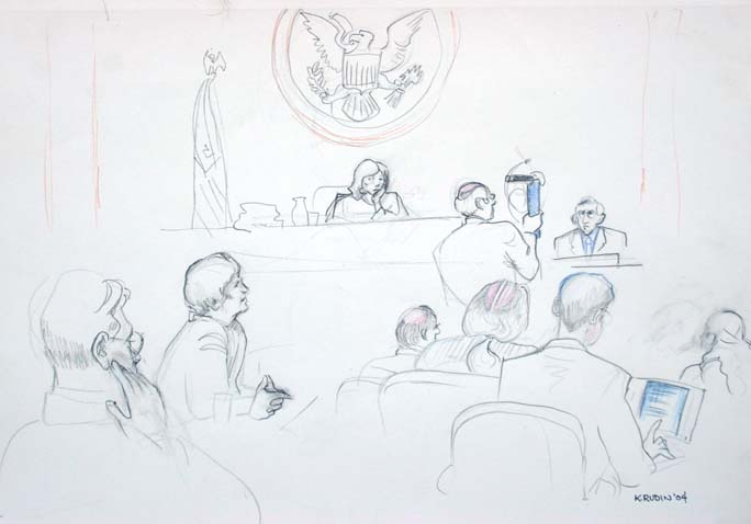 Defense attorney William Bragg questions former Sgt.Pete Ciarabellini while holding up a Makita electric grinder. In the foreground at left is the defense counsel table, and plaintiffs' counsel table is at right.